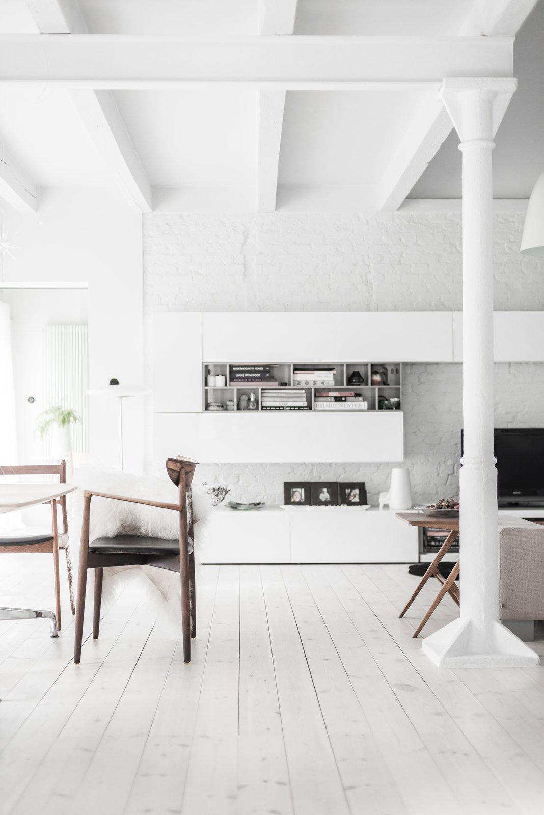 Dining Room, Table, and Chair White paint with just a hint of gray dominates the farmhouse, reflecting Kolasiński's love of bright spaces. The pine wooden floors were also enameled in a white oil imported from Denmark.  Photo 4 of 10 in A Run-Down Farmhouse Becomes a Sleek Modern Retreat