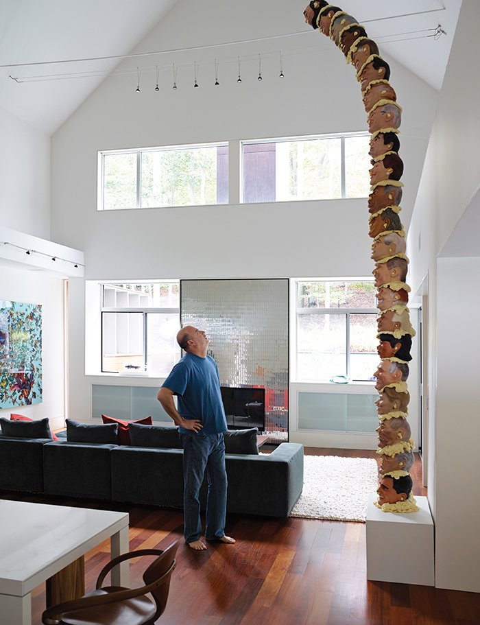 Living Room, Medium Hardwood Floor, Sofa, and Pendant Lighting Andrew Weinstein stands in the living room of his Long Island abode designed by Bates Masi + Architects. The architects toggled wall panels and panes of custom-cut window glass on the front of the house that let in light while leaving room for large-format artwork like Adam Parker Smith's American Totem.  Photo 2 of 12 in Art-Filled Hamptons Vacation Home