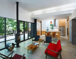 """Floor-to-ceiling windows, complemented by a wood-burning stove from Jøtul, bring the outdoors in. """"Movement throughout the house—down the hall, through a doorway, or across a room—is always toward a view of the outdoors, creating a connection between the inside and outside,"""" Hart says."""