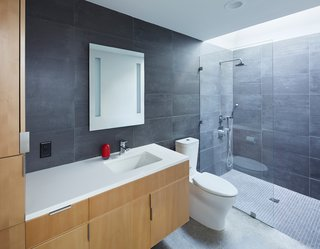 Made of stained beech wood with pulls by Mockett, the bathroom vanity was custom-designed by the architects. A Caesarstone counter, Toto sink fixture, Tech Lighting mirror, and Kohler toilet and sink are surrounded by Mosa tiles.