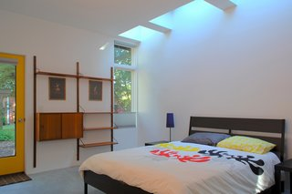 "In the bedroom, an IKEA bed frame and CADO wall unit are drenched with natural light during the day from the skylights overhead. ""The effect of daylight through skylights is very different than from a window,"" Hart says. ""You feel every minute of the day as light in the space ebbs and flows with the passing clouds."""