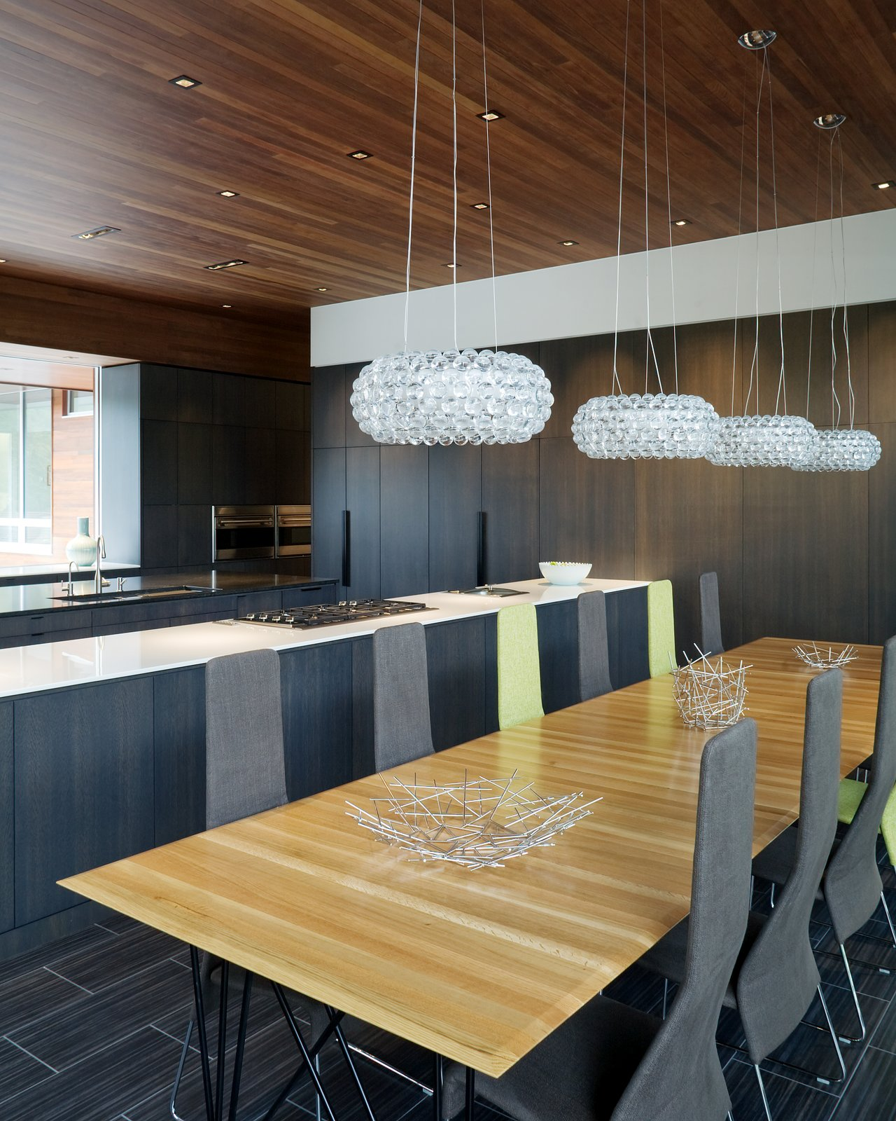 Adjacent to the internal courtyard, the long galley kitchen blends a mixture of dark materials and colors. The appliances are mostly concealed into the walls to create a clean, uncluttered atmosphere. The table was custom-made by Hufft.  Photo 4 of 10 in A Bold Home Creatively Combines Curves and Modern Lines