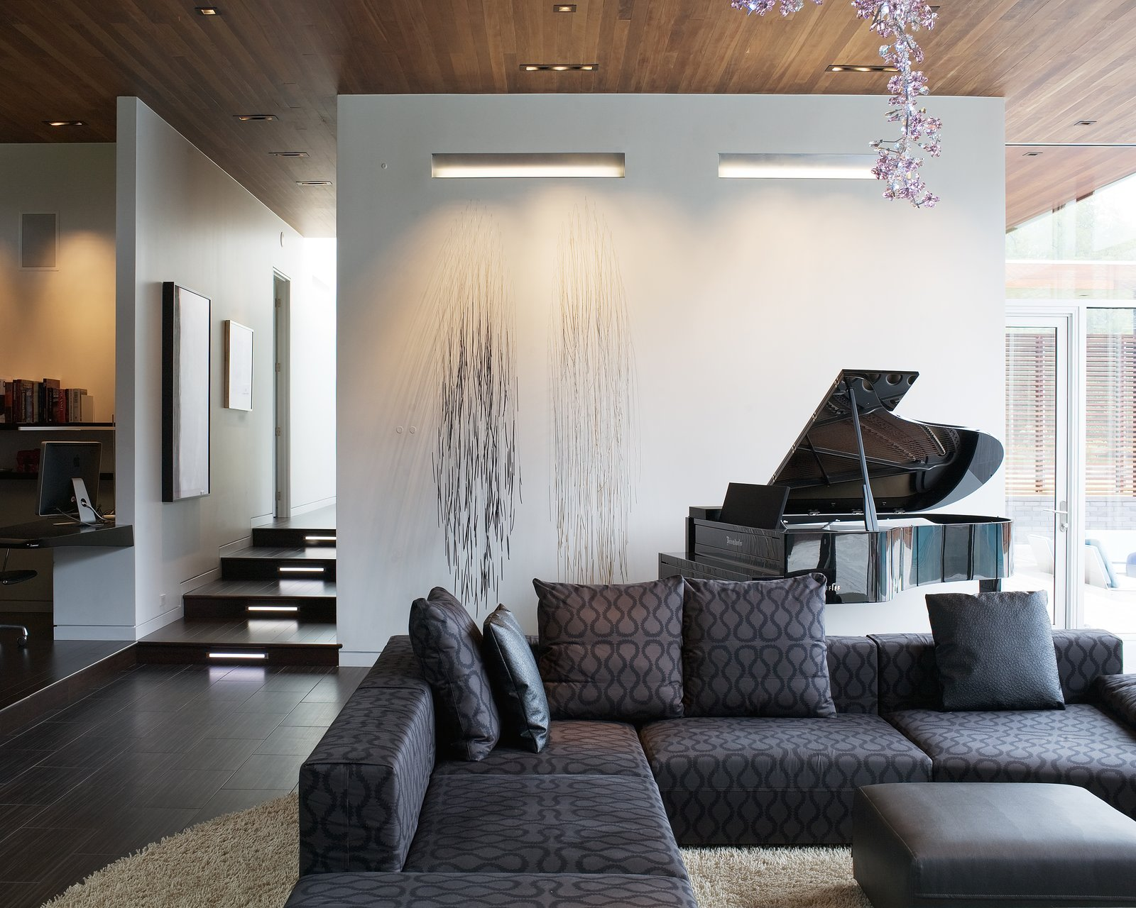 In the living room, several art installations add flair, including one special addition from Anne Lindberg, an artist known for understated line drawings. Strands of welding wire with tiny sculpted wood ends were drilled into the wall near the piano so they would stick out and move with breezes from the courtyard. Its cascading lines contrast directly with the curvilinear, soft pink Swarovski crystal chandelier by Tord Boontje.  Photo 6 of 10 in A Bold Home Creatively Combines Curves and Modern Lines