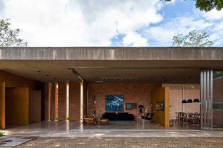This Cor-Ten House in Brazil Would Not Be Complete Without its Giant Home Library - Photo 5 of 7 - The home's living room can be kept open to the elements, or sectioned off with sliding glass walls. A natural concrete slab acts as an exterior barrier, and freijó wood and track lighting define the interior space. C10 sofa by Marcus Ferreira and vintage Poltrona Molé chair by Sergio Rodrigues provide casual seating. Across the partition wall, a Jader Almeida table anchors the dining room.