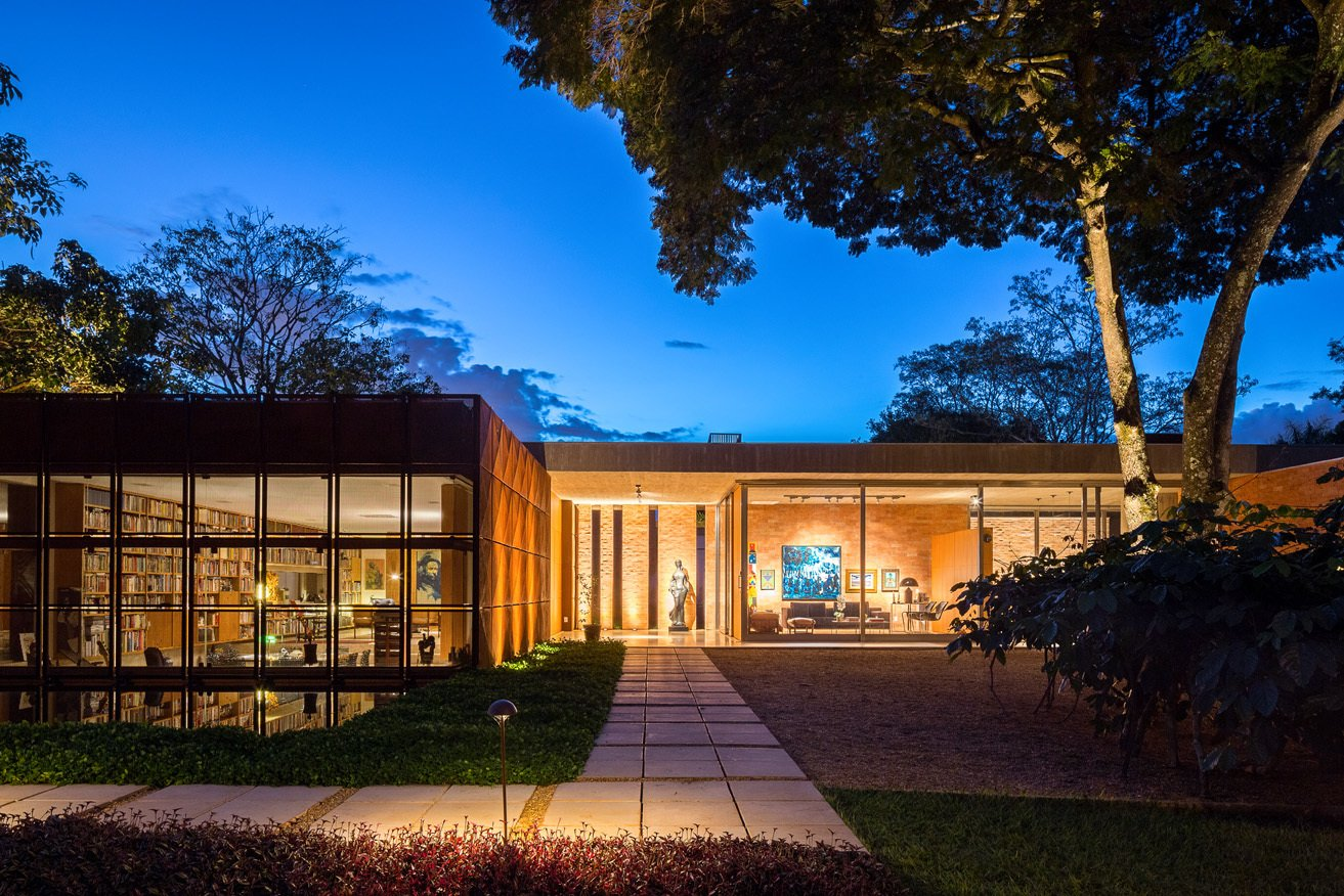 Exterior, House Building Type, Metal Siding Material, and Flat RoofLine With library's Cor-Ten shield open, the home's facade is seen at night. The L shaped pedestrian pathway forces visitors to travel around the perimeter before entry, gradually experiencing the architectural composition step by step.  Photo 3 of 7 in Modern Homes in Brazil from House of the Week: Indoor-Outdoor Brazilian Modern Home