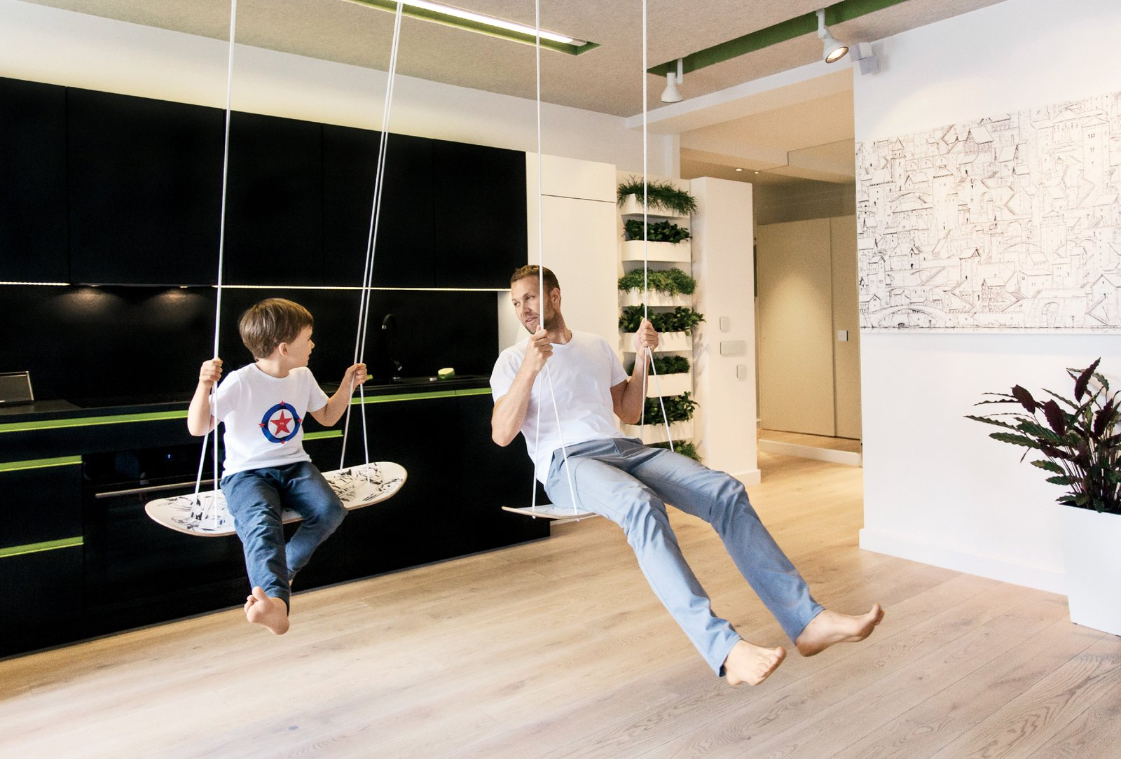 """Living Room, Track Lighting, and Light Hardwood Floor Inspired by skateboards, the swing seats are made of European oak. """"At first we tried bigger boards, but you can't sit on them,"""" Parzyszek says.  Photo 4 of 7 in 7 Minimalist Apartments Around The World from This Tiny Warsaw Studio Instantly Changes from Office to Playroom"""