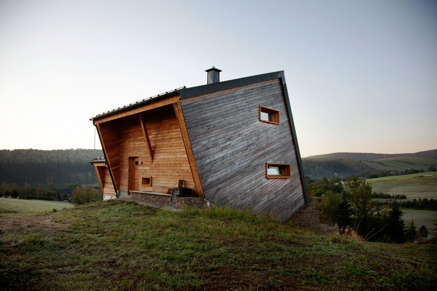 Exterior, Cabin Building Type, Tiny Home Building Type, Wood Siding Material, and Metal Roof Material Sebastian Heise's wooden structure, seemingly atilt, overlooks a green valley in Oberwiesenthal, Germany. The two horizontal windows on the side and the front porch give the home its own unique sense of balance.  Photo 25 of 101 in 101 Best Modern Cabins from Tour 8 Awesome Tiny Cabins Around the World