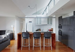 An Off-the-Grid Prefab that Combines Open Plan Living with Rugged Durability - Photo 6 of 10 - Inside, bar stools by Anibou, appliances by Miele, and gray cabinets from IKEA furnish a simple kitchen.