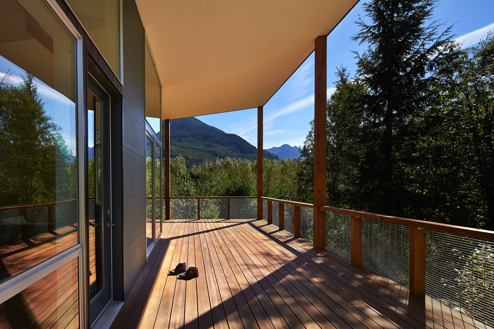 """""""I wanted to create 'defensible' outdoor rooms that flowed in and around the buildings,"""" Coleman said. The deck was built with Red Balau hardwood, which has a custom oil finish by Messmer's.  Photo 9 of 10 in This Retreat in the Cascades is a Bold Take on the Modern Cabin"""