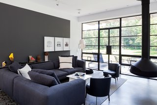 Situated near the south-facing facade, the main living space is furnished with a Michel sectional from B&B Italia, Feel Good side chairs by Flexform, and a suspended Ergofocus fireplace from Focus.