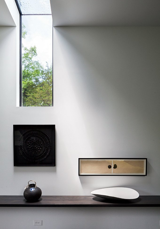 """The floor coverings are designed by Chilewich, and an assortment of art pieces decorates a wall-mounted, stained maple shelf in the hallway. Though it posed structural difficulties, the elongated, wall-notched skylight provides a magical moment, says Sultan: """"We can go to bed at night and see the moon through it.""""  Photo 3 of 12 in A Couple Takes an Unassuming Plot of Land and Calls it Home"""