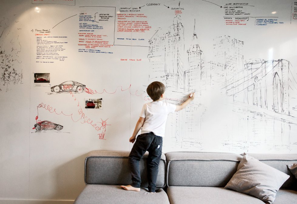Living Room and Sofa An entire wall is covered with a dry-erase surface from Formica, where Parzyszek and his son Bartek can sketch.  Photo 7 of 11 in 10 Best Dwell Studios and Modern Apartments from This Tiny Warsaw Studio Instantly Changes from Office to Playroom