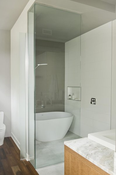 An Emily quartz bathtub by Caml-Tomlin is surrounded by Ceragres' fade and frammenti tile.