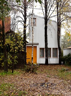 """Our goal was to construct a house with the lowest possible budget, while ensuring comfort and efficiency for the residents inside,"" says Sergey Kolchin, founder of Le Atelier. The architects accented the home's front door by painting it yellow, harmonizing the structure with the surrounding forest."