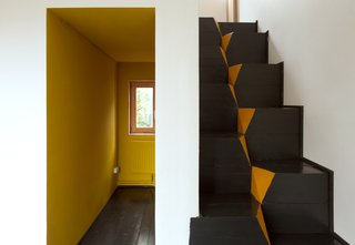 "A corridor-like entrance invites residents into the home. The architects chose to use goose-step stairs because of their safety and efficiency in compact spaces. ""This staircase is also the easiest in terms of construction,"" Kolchin says. ""It is nearly impossible to make any mistake while building it."""