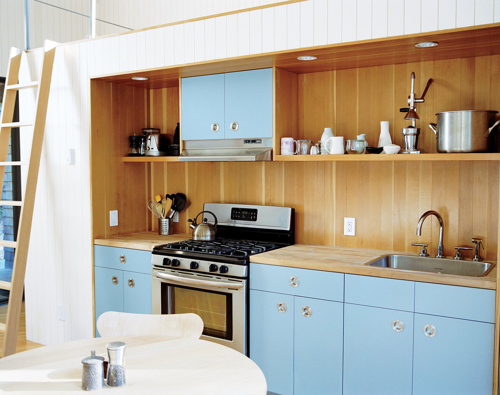 Kitchen, Colorful Cabinet, and Wood Cabinet The kitchen area, which has IKEA cabinets with custom doors and pulls by Doug Mockett, is also recessed, with a lofted area above it.  Photo 7 of 12 in This Tiny New England Cottage Is a No-Frills Weekend Hideaway