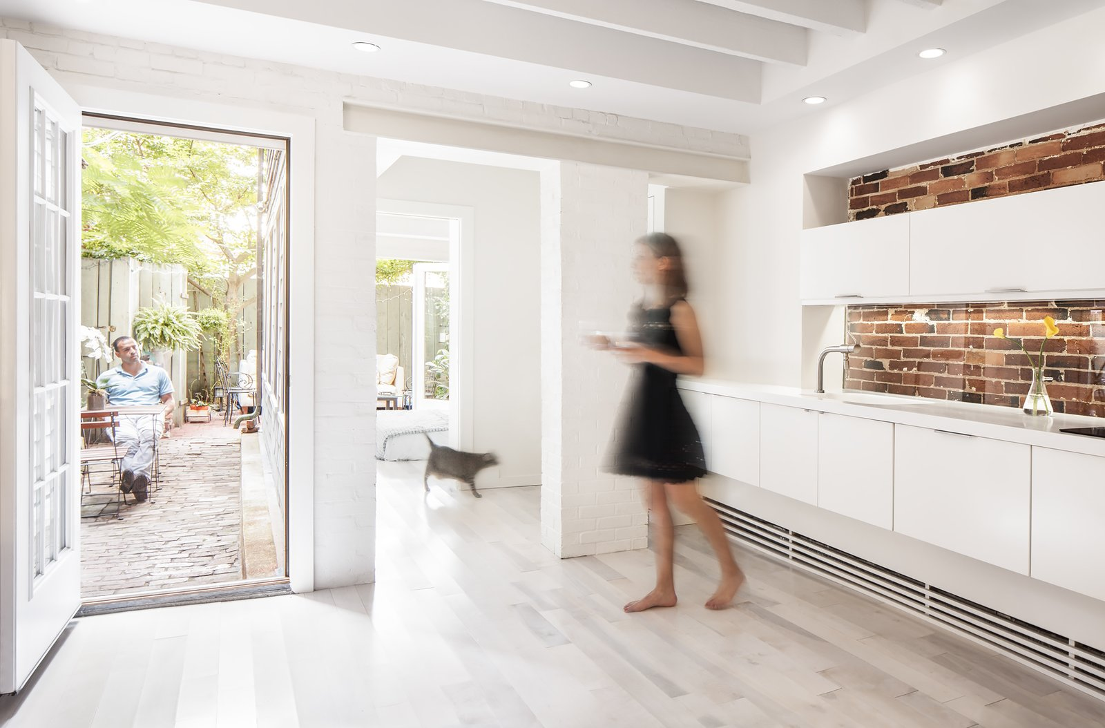 Kitchen, White Cabinet, Light Hardwood Floor, and Recessed Lighting Architects who practice in dense cities know its almost impossible to add square footage to an apartment. Yet at a garden-level residence in Boston's historic Beacon Hill neighborhood, Chris Greenawalt of Bunker Workshop was able to unearth 70 square feet of living space through a little excavation.  Photo 1 of 5 in An Archaeological Renovation Adds Precious Space to a Tiny Boston Apartment from Beacon Hill