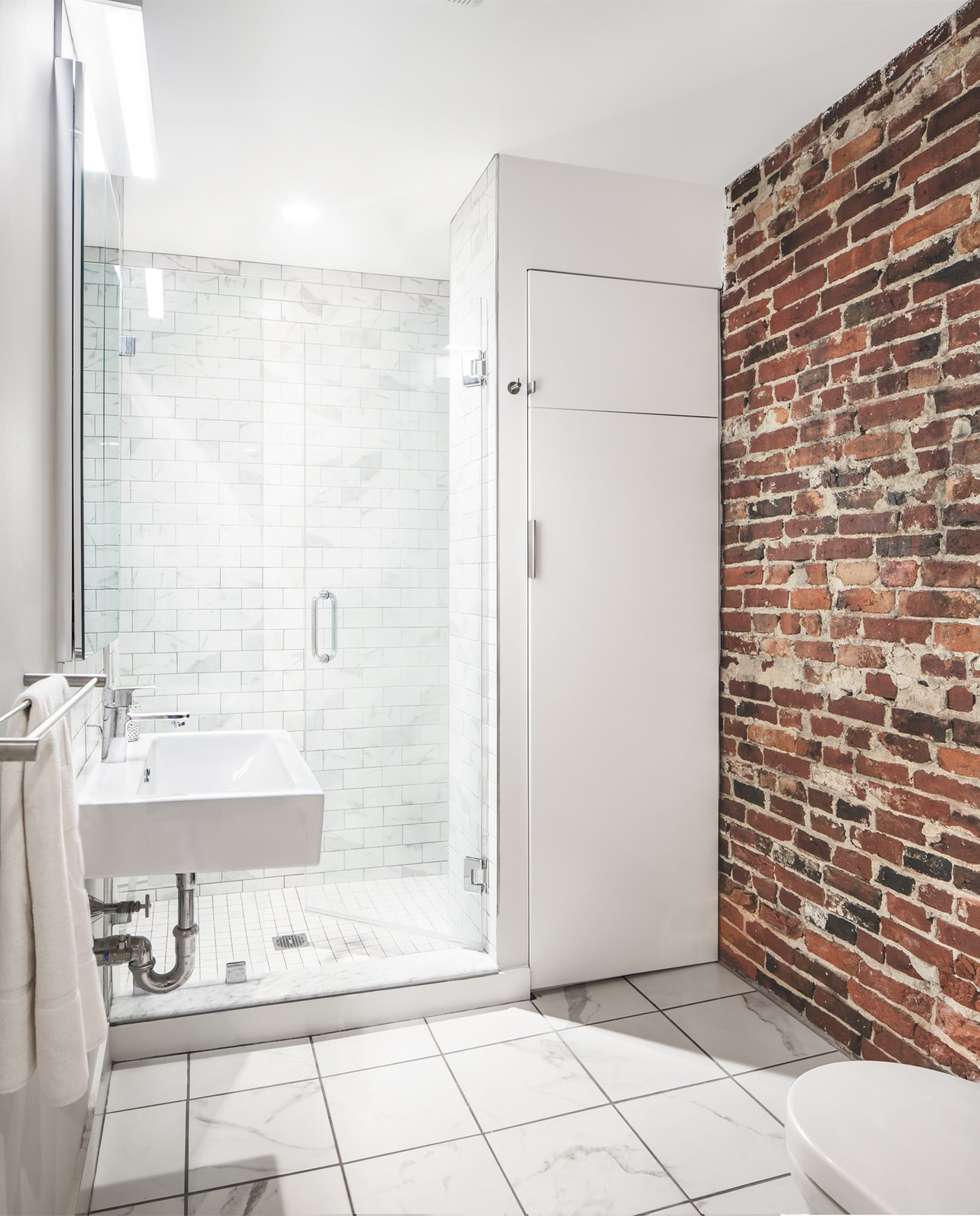 Bath Room, Enclosed Shower, Porcelain Tile Floor, and Wall Mount Sink Along with historic wood and steel details, several warm brick walls were exhumed and left exposed.  Photo 4 of 5 in An Archaeological Renovation Adds Precious Space to a Tiny Boston Apartment from Beacon Hill