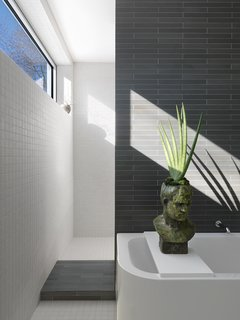 Ann Sacks and American Olean porcelain tile cover every square inch of this elegant, minimalist master bathroom.