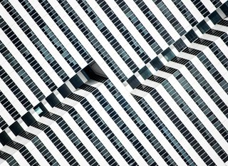 """Hypnotic Building, 2014. """"The saturated facade of this late-modernist 1981 office building in Houston, Texas, exposes the inner paths of its elevators, outlining the dramatic black-and-white lines with glass and aluminum,"""" notes Olic."""