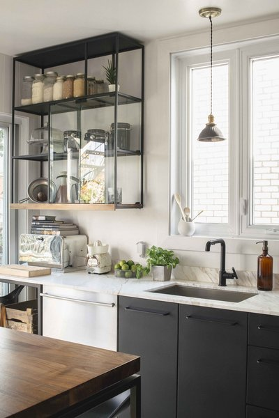 Havart designed the open shelving, which is coated with the same black finish as the cabinets. The lowest, walnut shelf matches the adjacent kitchen table.