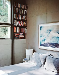 """In the master bedroom, above the Legnoletto by Alias bed, is a photograph by John Huggins. The lamp is from Ikea. """"Nothing is painted—all that stripping is about getting to the natural surfaces of the wood, and the concrete block,"""" Norelius says."""