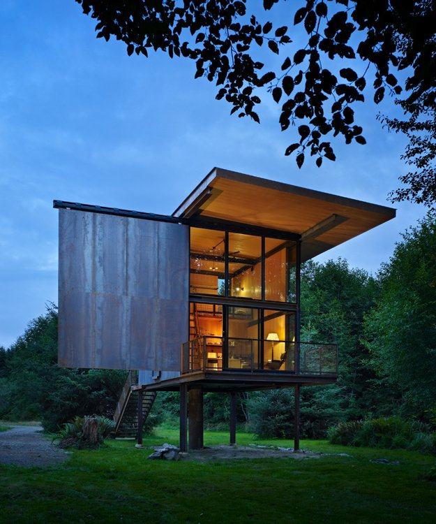 Exterior, Cabin Building Type, Glass Siding Material, and Metal Siding Material At just 350 square feet, this remote cabin with a view for the Sol Duc River sits on stilts to protect it from flooding and the dampness of the northwestern rainforest. Its shutters can be operated manually by custom steel rods.  Photo 63 of 101 in 101 Best Modern Cabins from Discover the Work of a Leading Seattle Modernist