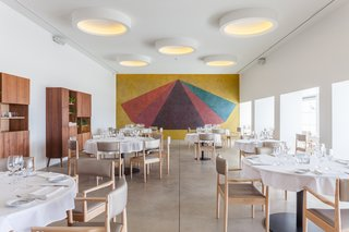 In the dining room, a mural by Sol LeWitt, painted in 1990, was uncovered. A circular theme, introduced in the original project, is reinforced by round lamps throughout the interior.