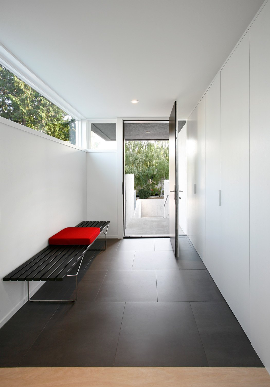 """""""A series of stepped concrete site walls lead you gradually up to a covered exterior entry, which opens onto a compressed entry foyer,"""" Hutchison says. A Bertoia bench by Knoll sits in an entryway covered by Mosa's Greys Collection tiles.  Photo 7 of 11 in 10 Fantastically Sleek Foyer Designs from Portage Bay Bungalow"""