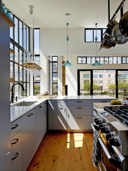 Kitchen The kitchen is marked by its Wolf gas range, white Carrara marble countertop bar, and Cobb Rise & Fall pendants by Original BTC. The architect designed a custom wine glass holder, which hangs nearby.  Photo 19 of 20 in 20 Best Modern Kitchen Counters