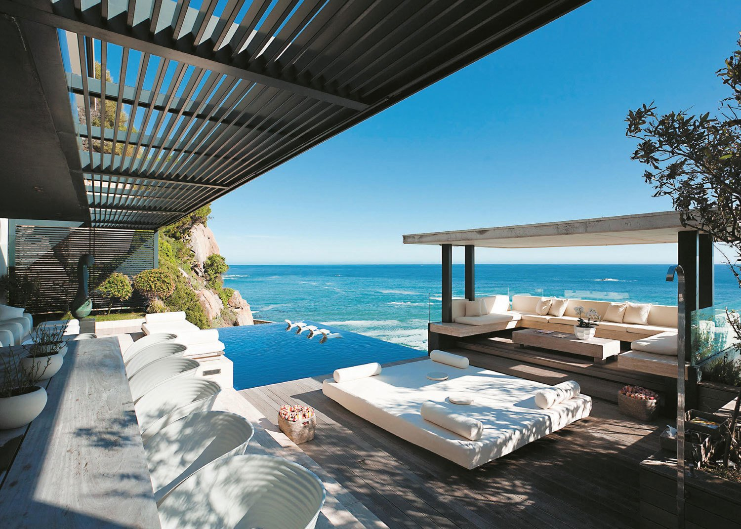 A home in Cape Town by SAOTA combines all of the indoor and outdoor living and dining areas on the ground floor, in order to create a thriving area for entertaining and relaxing by the sea.  Photo 10 of 13 in 12 Perfect Plunge Pools For Your Small Outdoor Space from Amazing Waterfront Residences Around the World