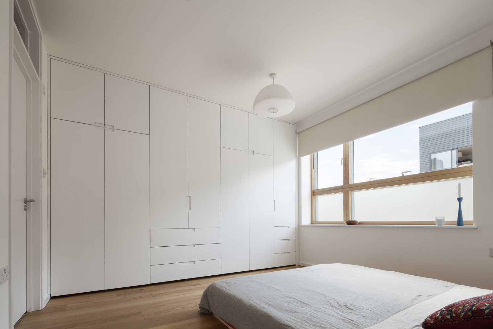 The entrance level's master bedroom has engineered oak floors and a full wall of built-in closets.  Photo 6 of 7 in A Clever Sunken Roof Fills a London Terrace House with Light
