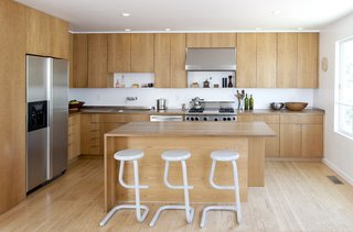Movable and space-saving design elements define this creative family home in the city's Mission District. The kitchen was given an economical revamp by adding new drawer and door fronts to the existing cabinet boxes. Countertops were replaced with custom fabricated butcher-block surfaces, and a complementary white-oak kitchen island was installed. A Wolf range, Vent-a-Hood hood, Franke stainless steel sink, and Bosch dishwasher complete the stylish new space.