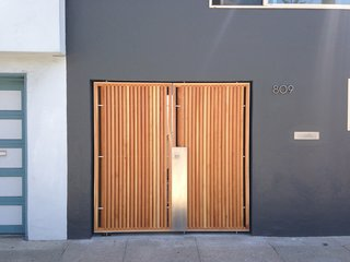 The focal point of the home's modernized exterior is a custom, wood-and-steel entry gate designed by atelier KS and built by DeFauw Design + Fabrication, a local fabricator who also made custom closing hardware for the piece. Franz and Paré-Mayer paired angled cypress slats with an industrial metal frame to create the entryway. A few paces behind the gate, a large glass door provides direct access to the home, fulfilling the owners' wish for an entry vestibule that would be separate from the street. The angled wood slats offer privacy from the exterior, while selectively allowing light to penetrate through.