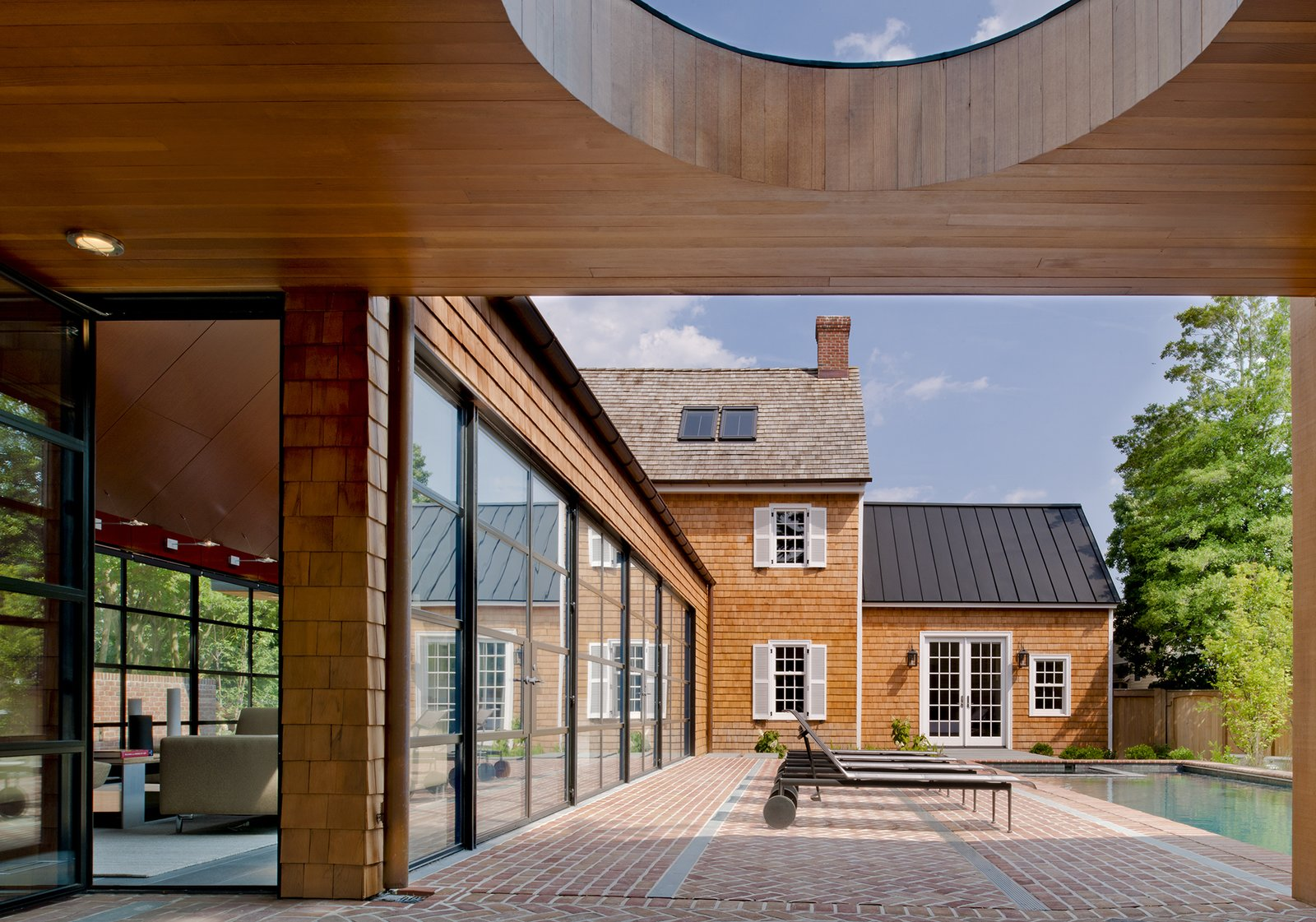"""""""The client wished to more that double the size of the house,"""" Gurney said. """"The goal was to provide the additional space as a series of smaller pavilions to allow the original historical house to be the most important part of the composition."""" Steel swing doors by Hope's Windows Inc. lead outside, and a custom standing seam metal roof slopes above the far end of the pool.  Brilliant Examples of Indoor-Outdoor Homes by Zachary Edelson from A Traditional Facade Hides A Light-Filled Modern Delaware Renovation"""