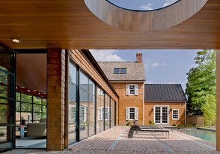 """""""The client wished to more that double the size of the house,"""" Gurney said. """"The goal was to provide the additional space as a series of smaller pavilions to allow the original historical house to be the most important part of the composition."""" Steel swing doors by Hope's Windows Inc. lead outside, and a custom standing seam metal roof slopes above the far end of the pool."""