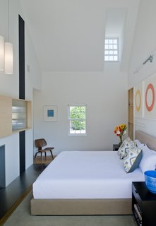 """In this project, the interior walls and ceilings in the existing historical component are white, and the walls and ceiling materials in the new pavilions are wood,"" Gurney said. In the master bedroom, a custom bed and nightstands by Baron Gurney Interiors sit across from an Eames molded plywood lounge chair."