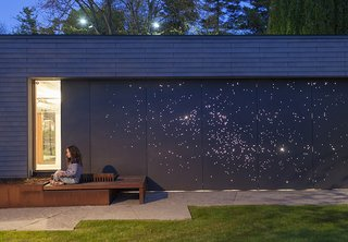 Architect Janna Levitt laser cut an astral pattern into the garage door of this renovated Toronto home, installing LED lights behind the fiber-cement surface to complete her depiction of the constellations Sagittarius and Scorpio.