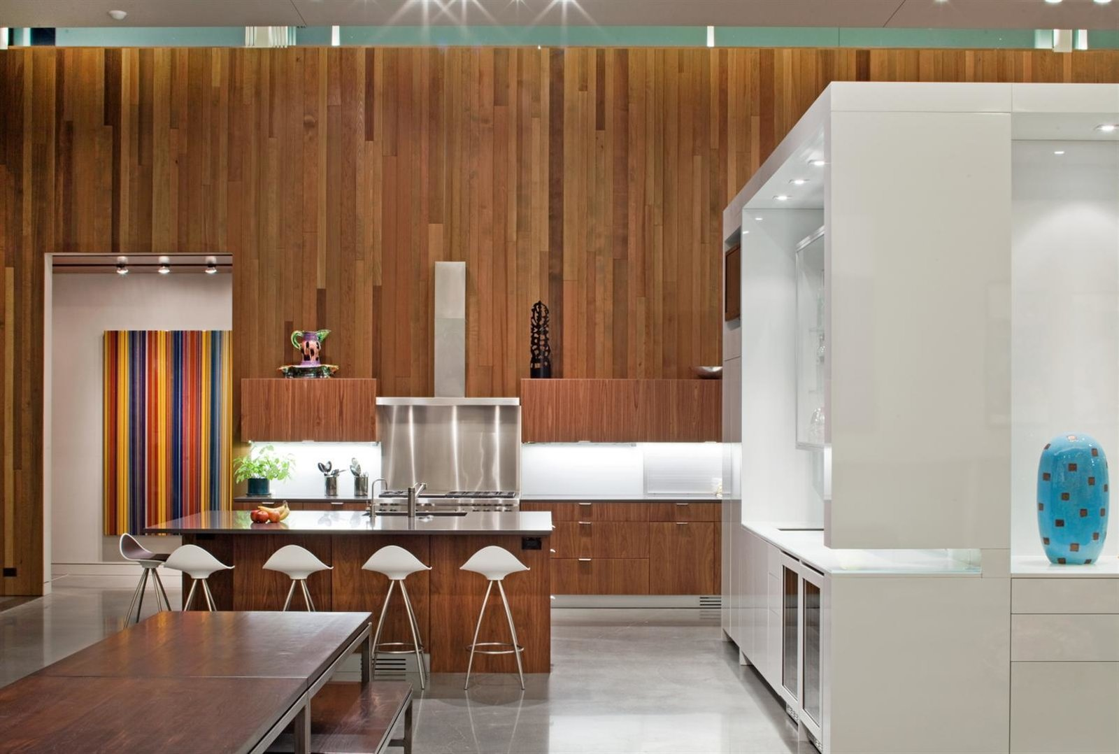 """The house features 16-foot-high ceilings and is heated and cooled primarily from geothermal ground loops, with radiant lines inside the concrete floors. A central """"cube"""" designed and fabricated by the architects offers pantry storage and delineates the kitchen, living, and bar areas. The glossy sheen comes courtesy of white automotive paint.  Photo 11 of 12 in Material Spotlight: 11 Hardworking Uses of Western Red Cedar from Omaha Art-Inspired House"""