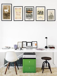 In the office, which is part of the addition, a collection of vintage posters hangs above a Cbox file cabinet and a table from Blu Dot used as a desk. The rug is a Photon.
