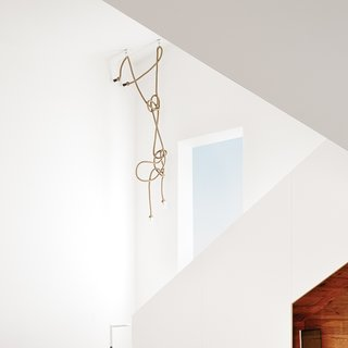 The stairway chandelier is made from designer Christien Meindertsma's flax-rope lamps for Thomas Eyck, which feature the same material as those used in Dutch shipping yards. At eight months pregnant, in anticipation of the new baby, Suttles mounted a ladder to arrange the rope, which her stepmother strategically sewed to achieve just the right shape.