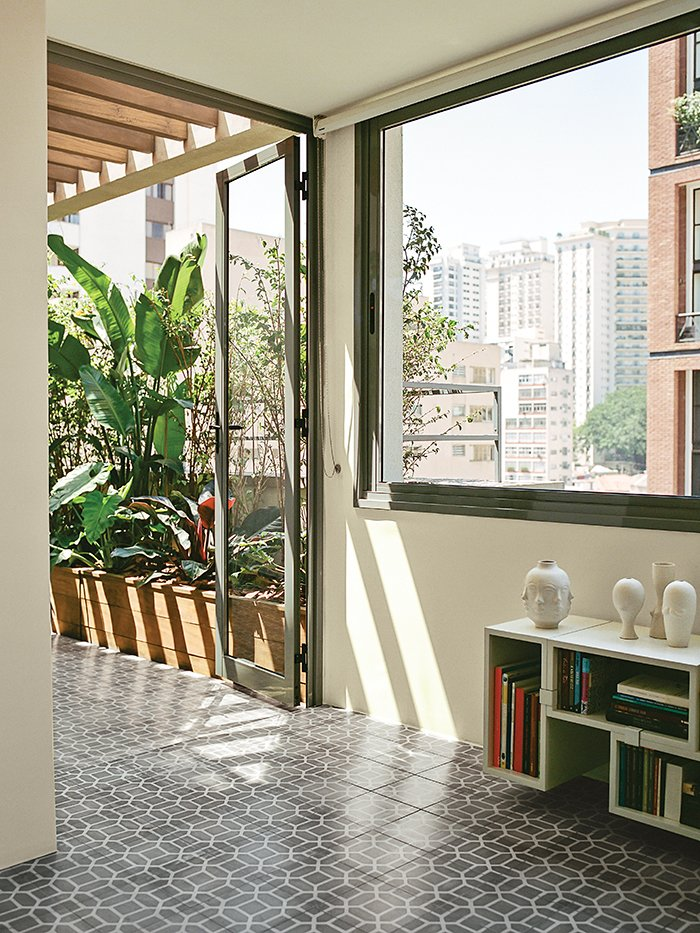Living Room, Storage, Shelves, and Bookcase A Muuto Stacked shelf system hugs the wall beneath the window in the dining room.  Photo 9 of 15 in Amazing Garden Oasis in São Paulo Born from a Five-Year Search and Renovation