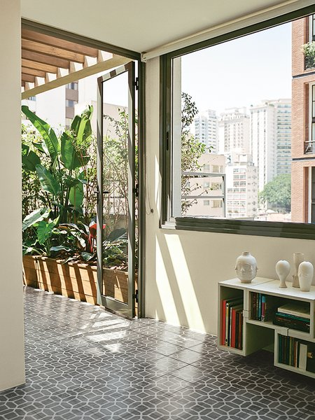 A Muuto Stacked shelf system hugs the wall beneath the window in the dining room.  Photo 9 of 15 in Amazing Garden Oasis in São Paulo Born from a Five-Year Search and Renovation