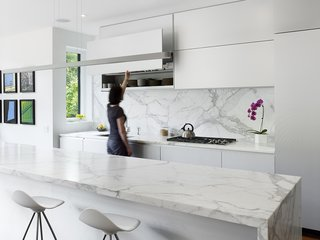 The kitchen contains Onda barstools by Stua from Design Within Reach that surround a 13-foot Calacatta marble island. Custom white aluminum cabinets float above the kitchen appliances by Miele with a stovetop from Wolf and a range hood by Airmec Bello.