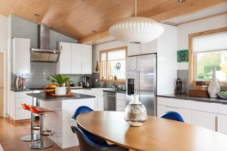 The kitchen features Ikea Sektion cabinets and Whirlpool appliances. The dining area contains a table from CB2, a George Nelson pendant, and Eames molded fiberglass chairs that were picked up at the Alameda Flea Market.
