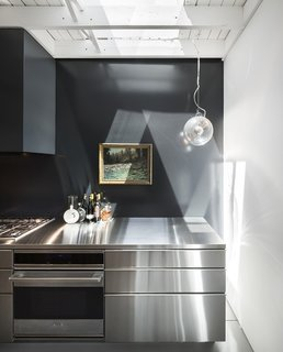A close-up of the steel counter shows the Artemide Miconos lamp hanging near the sink, as well as the diffused light that streams in via a set of skylights arranged throughout the roof.