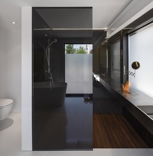 In the bathroom, a small bioethanol EcoSmart burner, along with radiant hydronic in-floor heating, provides warmth in a stark space.