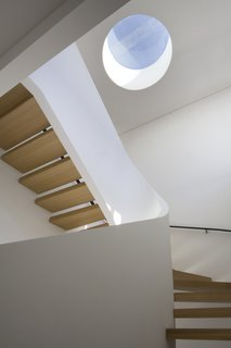 A small circular skylight serves as a vertical focal point in the center of this stairwell, and provides much-needed natural light. The white walls of the stairs bounce light, but the darker wood treatment ensures that the space is not too bright.