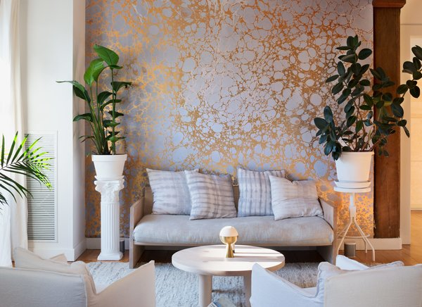 An installation of Wabi River, a silver-and-gold marbled mural by Calico Wallpaper, cofounded by residents Rachel and Nick Cope, forms a palette of coordinated tones in the living area. Nearly all of the furnishings in the apartment are by friends and peers of the local New York design scene: The daybed sofa is by Farrah Sit, the hand-dyed shibori pillows are by Rebecca Atwood, the coffee table is by Fort Standard, and the incense burner is by Apparatus.