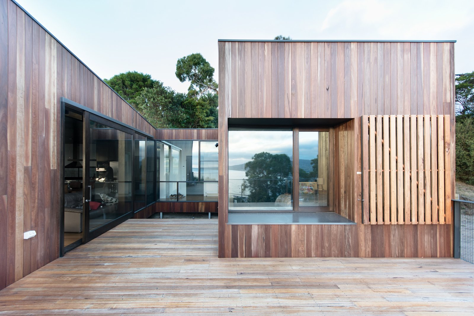 Outdoor, Large Patio, Porch, Deck, Back Yard, Trees, Wood Patio, Porch, Deck, and Metal Fences, Wall Operable timber shutters and screens offer protection from extreme weather. Zoning the house into three distinct masses creates a partly sheltered courtyard to make this year-round blending of the indoors and outdoors possible.  Photo 1 of 8 in An Australian Beach Home with Stunning Ocean Views from Martha